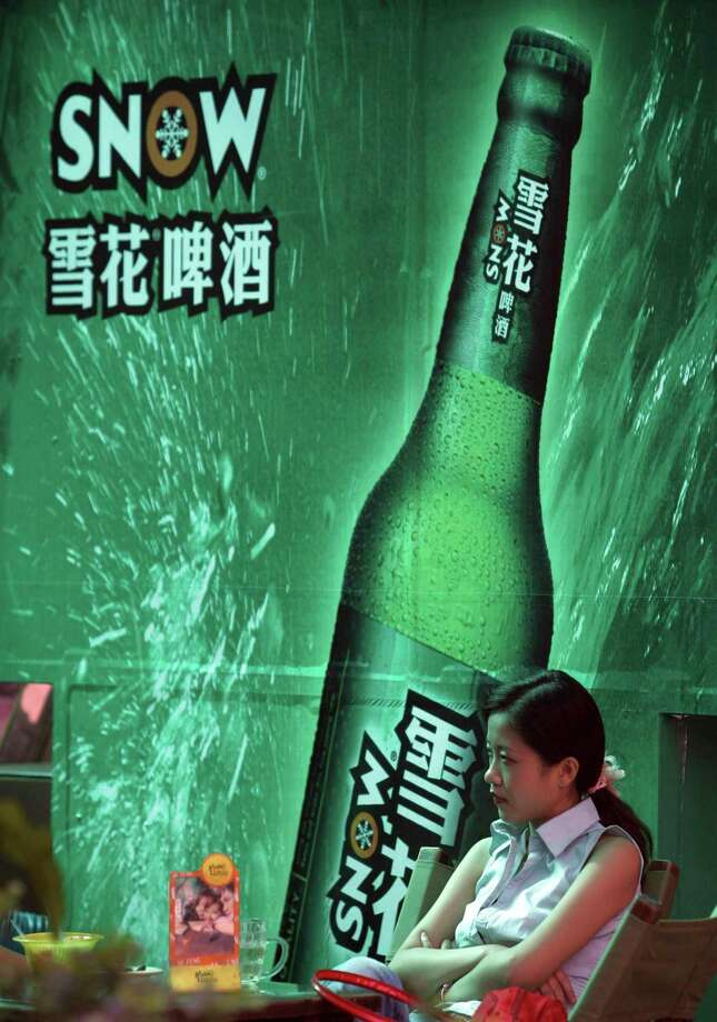 In this Sept. 11, 2006, photo, a woman sits near an advertising poster for Snow Beer in a bar in southwestern China's Chongqing municipality. A potential prize for AB InBev in its bid for SABMiller is a Chinese beer, Snow, that is the world's biggest seller. But any deal will face Chinese regulators who have barred the two brewing giants in the past from cooperating. Photo: Chinatopix Via AP    / CHINATOPIX