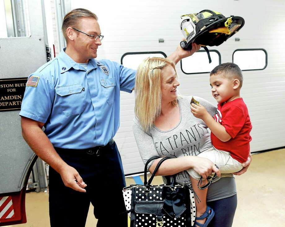 Hamden Fire Lt. Matthew Sarracco places a fire helmet on Christian Reynoso's head at the Hamden Fire Department Headquarters. At center is Christian's mother, Kate Annunziato. Photo: Arnold Gold — New Haven Register