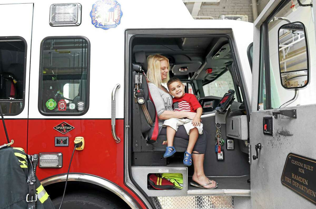 Kate Annunziato of Hamden sits with her son, Christian Reynoso, 4, in a firetruck at Hamden Fire Department Headquarters.