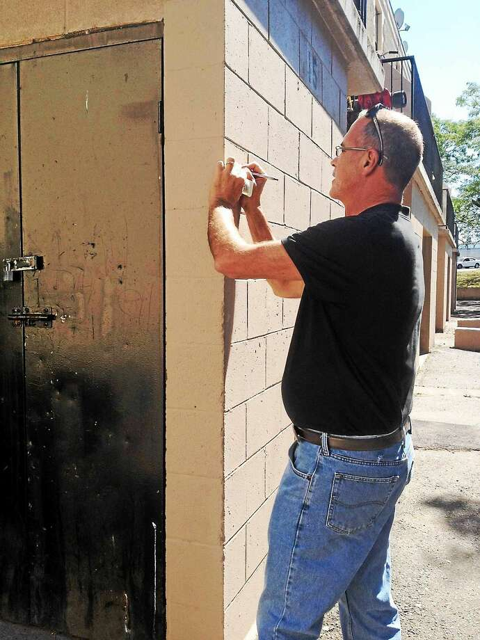 New Haven Building Official Jim Turcio makes a note outside a Station Court apartment on Tuesday. Photo: Mary O'Leary — New Haven Register