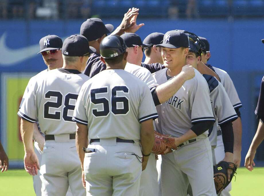 Yankees' starting pitcher Masahiro Tanaka is congratulated by teammates after beating the Blue Jays on Saturday. Photo: Fred Thornhill — The Canadian Press Via AP   / CP