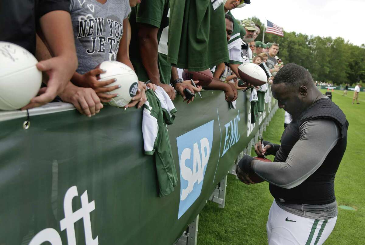 Jets defensive end Muhammad Wilkerson signs autographs for fans after a practice earlier this August.
