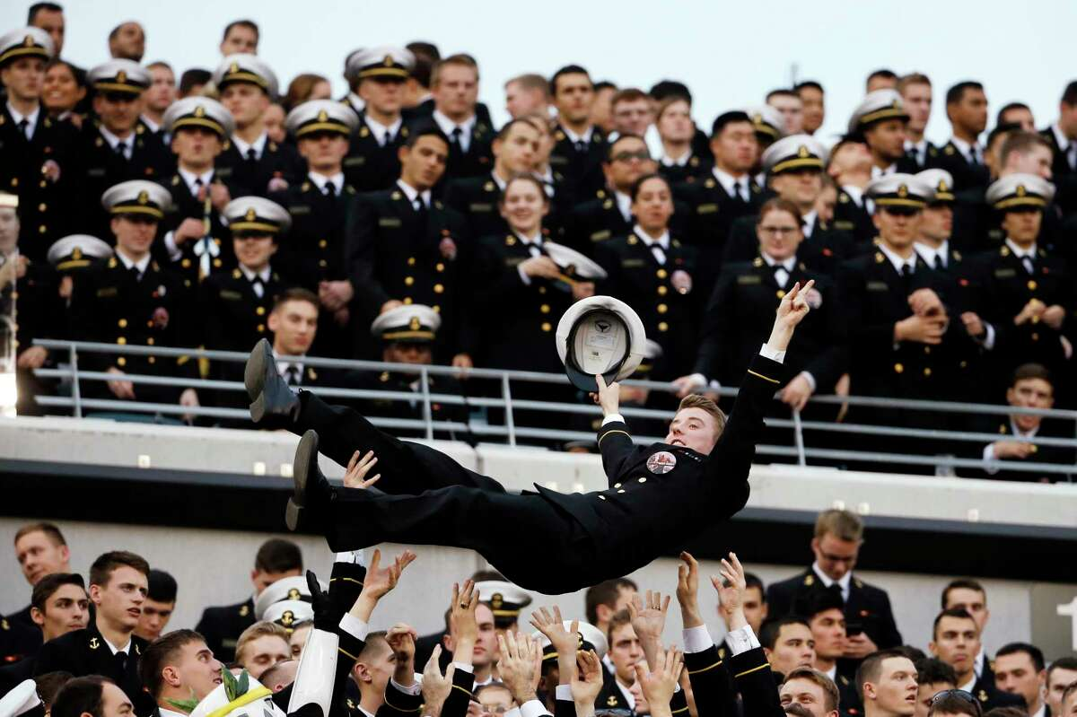 A Navy Midshipman is tossed in the air as Navy fans celebrate a touchdown during Saturday's game in Philadelphia.