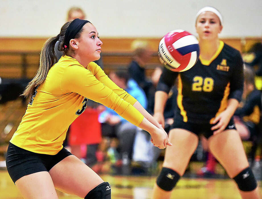 Amity's Brooke Matyasovky (28) keeps her eye on the ball as her teammate Cassidy Kirby bumps a shot up to the net in Wednesday's matchup against Hand. Photo: Catherine Avalone – New Haven Register   / New Haven RegisterThe Middletown Press