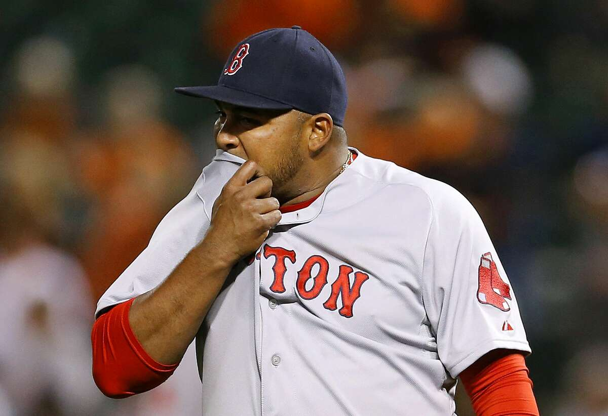 Red Sox relief pitcher Jean Machi wipes sweat from his face after the Orioles' Chris Davis scored on Adam Jones' double in the seventh inning on Monday.