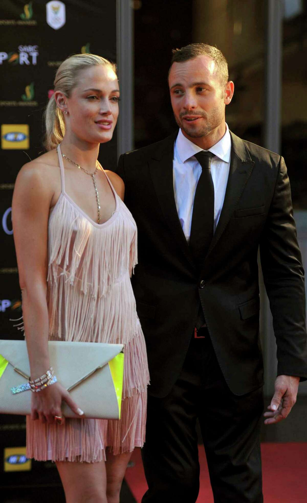 In this Nov. 4, 2012 file photo, South African Olympic athlete Oscar Pistorius and Reeva Steenkamp arrive for an awards ceremony in Johannesburg, South Africa. South Africa's Department of Corrections says a parole board has decided that Oscar Pistorius can be released from prison and moved to house arrest on Tuesday, Oct. 20 2015. The parole board made the decision Thursday, Oct. 15, 2015 after an initial decision to release the double-amputee runner in August was canceled. The Olympic runner has served nearly a year of his five-year sentence for manslaughter for killing Steenkamp.