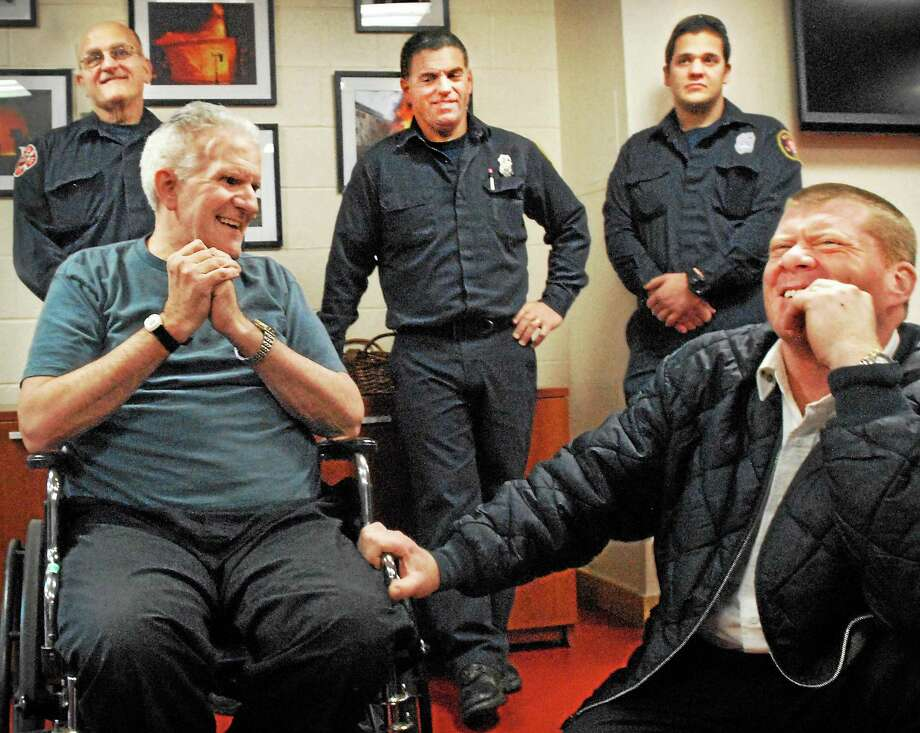 Former police officer William Stewart, seated at left, talks with Branford Deputy Chief Ron Mullen in 2012 after Stewart came to the fire headquarters to thank the emergency responders who saved his life after a brutal beating. At rear, from left, are firefighters Paul Cipriani, Dan Ghiroli and John Cudgma Jr. Photo: MELANIE STENGEL — NEW HAVEN REGISTER FILE PHOTO