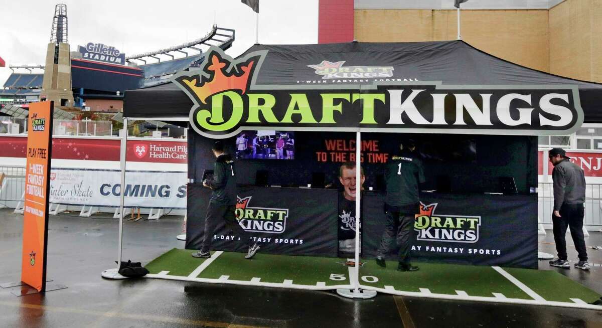 In this Oct. 25, 2015 photo, workers set up a DraftKings promotions tent in the parking lot of Gillette Stadium, in Foxborough, Mass. before an NFL football game between the New England Patriots and New York Jets. New York's attorney general on Tuesday, Nov. 10, 2015, ordered the daily fantasy sports companies DraftKings and FanDuel to stop accepting bets in the state, saying their operations amount to illegal gambling.