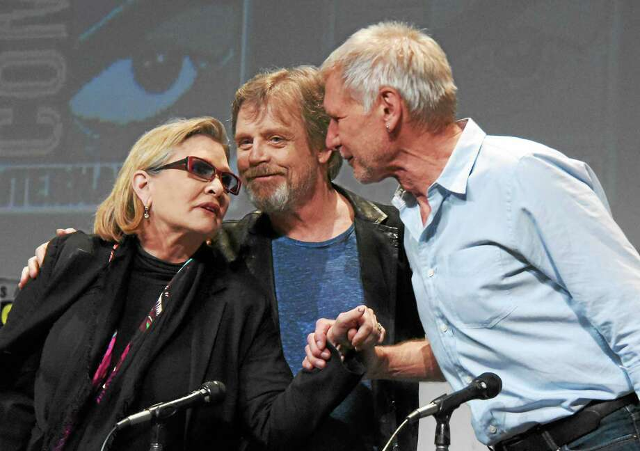 """Carrie Fisher, Mark Hamill, and Harrison Ford attended Lucasfilm's """"Star Wars: The Force Awakens"""" panel on day 2 of Comic-Con International in San Diego this July. Ford stars as Hans Solo in the new film, """"Star Wars: The Force Awakens,"""" opening here Friday. Photo: Richard Shotwell - Invision/AP   / Invision"""