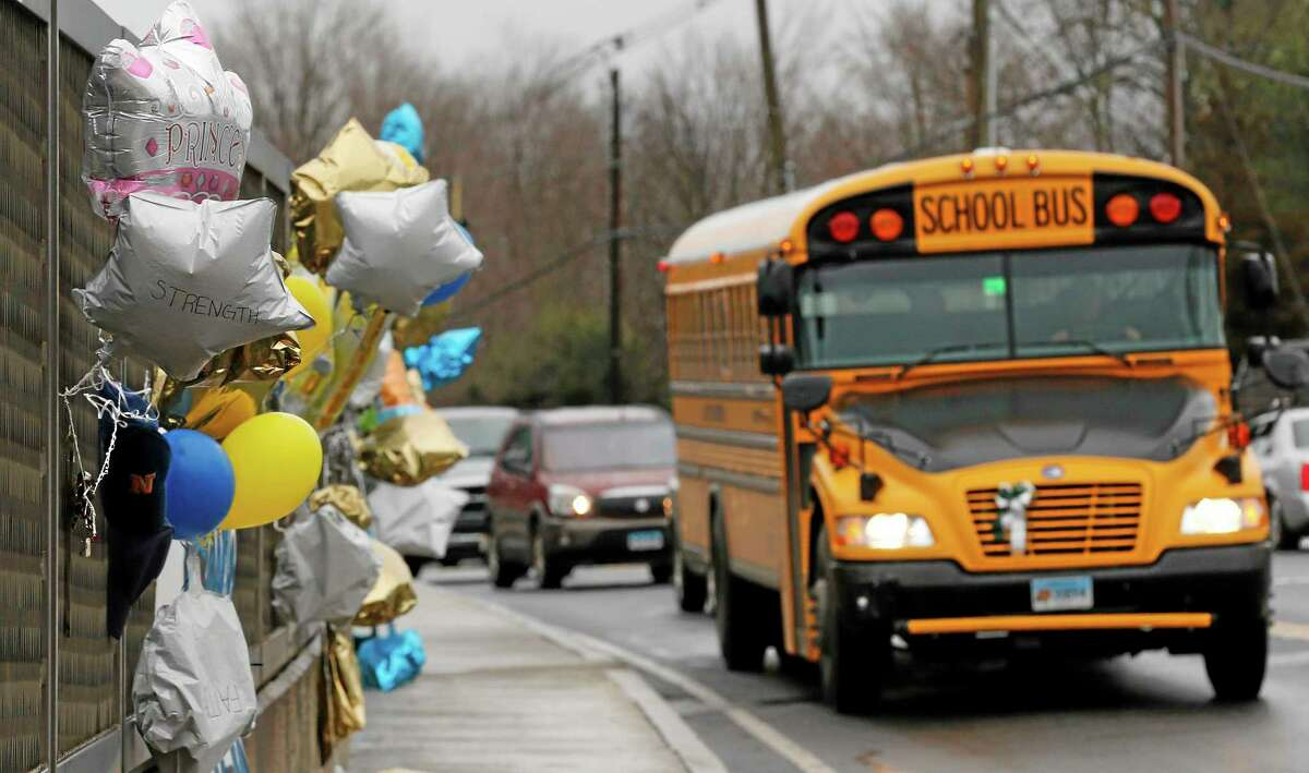 In this Dec. 18, 2012 photo, a school bus rolls toward a memorial in Newtown, Conn., for victims of the Sandy Hook Elementary School shooting.