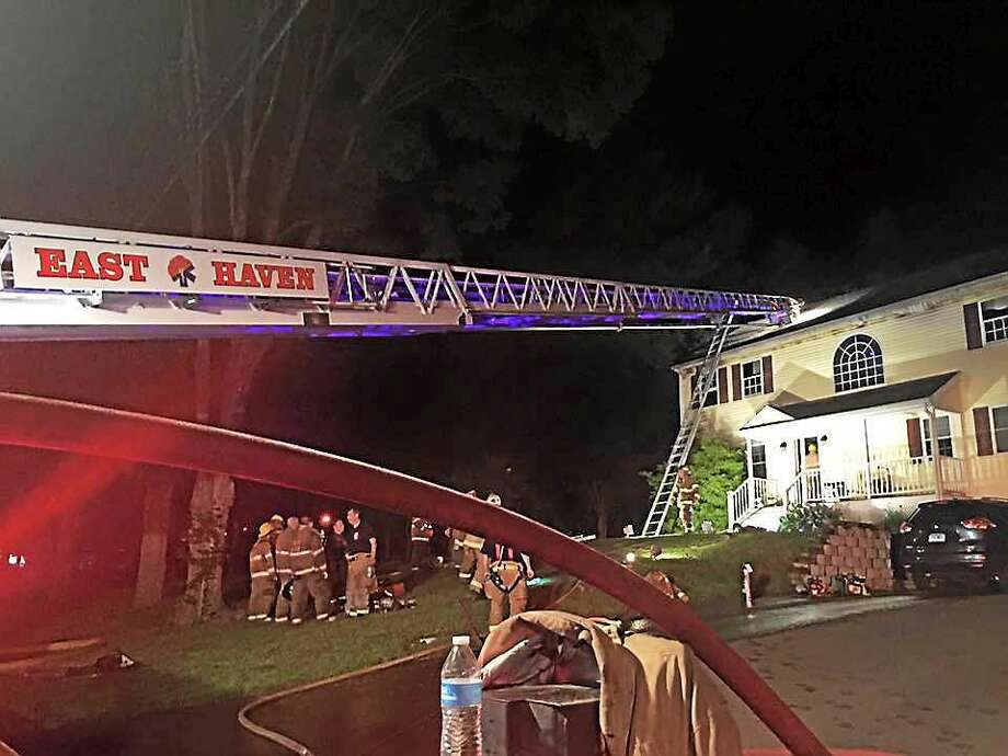 East Haven firefighters battled a fire Tuesday night at a home on Thompson Street. A firefighter was injured and a cat died in the fire, but three other pets were rescued. Photo: Photo By Matt Muolo Via East Haven Firefighters Local 1205