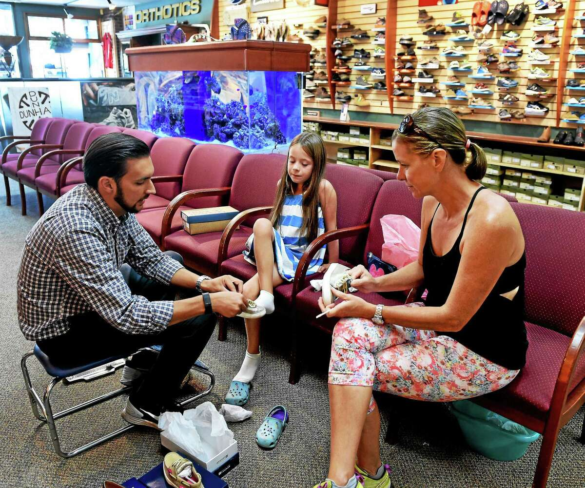 Jaime Bean, an employee of Arciuolo's Shoes in Milford, helps customer Allison Kreitler of Milford choose shoes for her daughter Haley, 6, during a visit to the store Thursday.