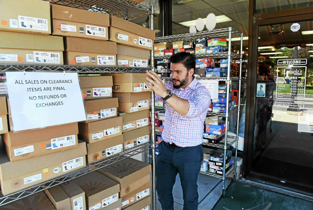 Matt Arciuolo, Jr. of Arciuolo's Shoes in Milford, checks inventory during a street sale at the store Thursday.