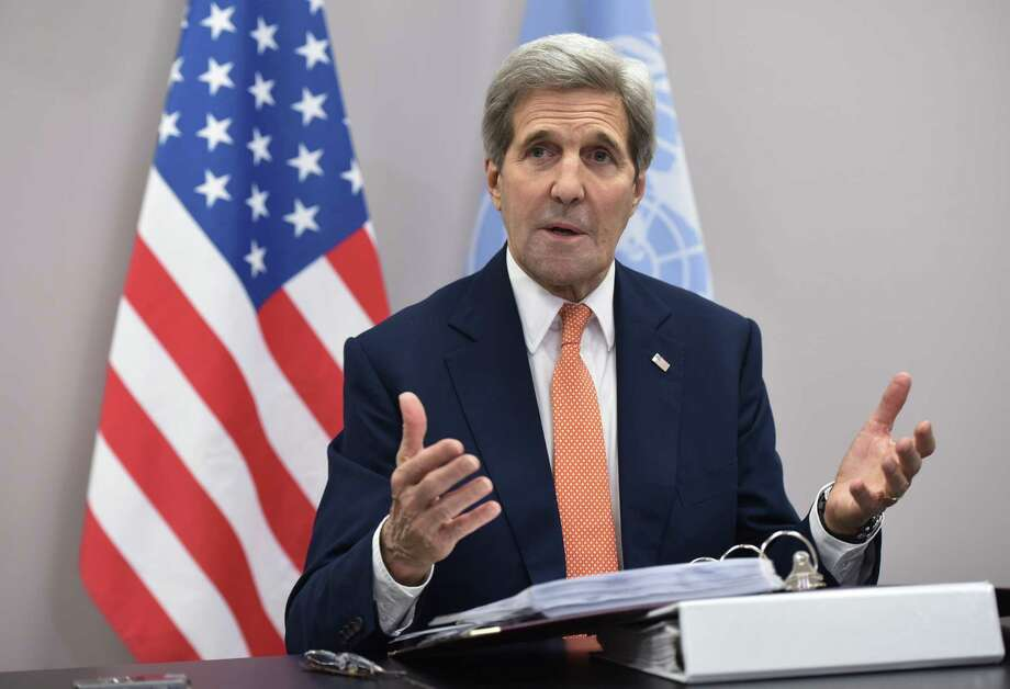"""US Secretary of State John Kerry speaks to the traveling press following the COP21 United Nations conference on climate change in Le Bourget, near Paris, Saturday. Kerry hailed Saturday's climate agreement as """"a victory for all of the planet and for future generations."""" He added it will """"prevent the worst most devastating consequences of climate change from ever happening."""" Photo: Associated Press   / Pool AFP"""