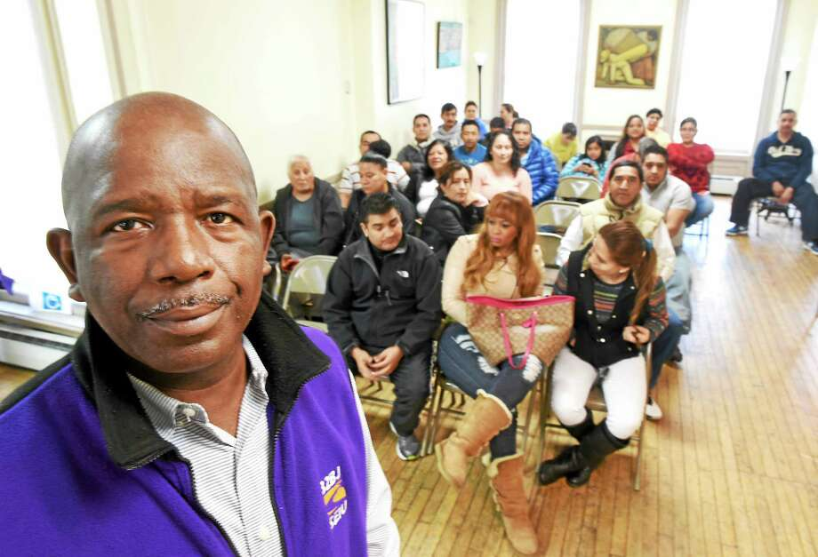Alberto Bernardez, assistant supervisor of SEIU Local 32BJ of commercial building janitors union, stands with some of the union members who voted to authorize strike after a vote at the New Haven People's Center Saturday. Photo: Peter Hvizdak — New Haven Register   / ©2015 Peter Hvizdak