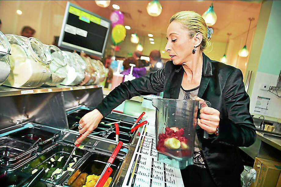 Las Vegas resident Magdalena Stojanovski, co-owner of Tropical Smoothie Cafe creates the Paradise Point smoothie made with strawberries, banana and pineapple at the grand opening Tuesday in New Haven. Photo: Catherine Avalone -- New Haven Register