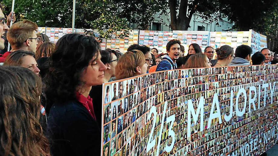 Members of GESO-Unite Here delivered a 15-foot photo petition bearing the faces of hundreds of Yale graduate student employees to the university's president and secretary Thursday. Photo: Ryan Flynn — New Haven Register