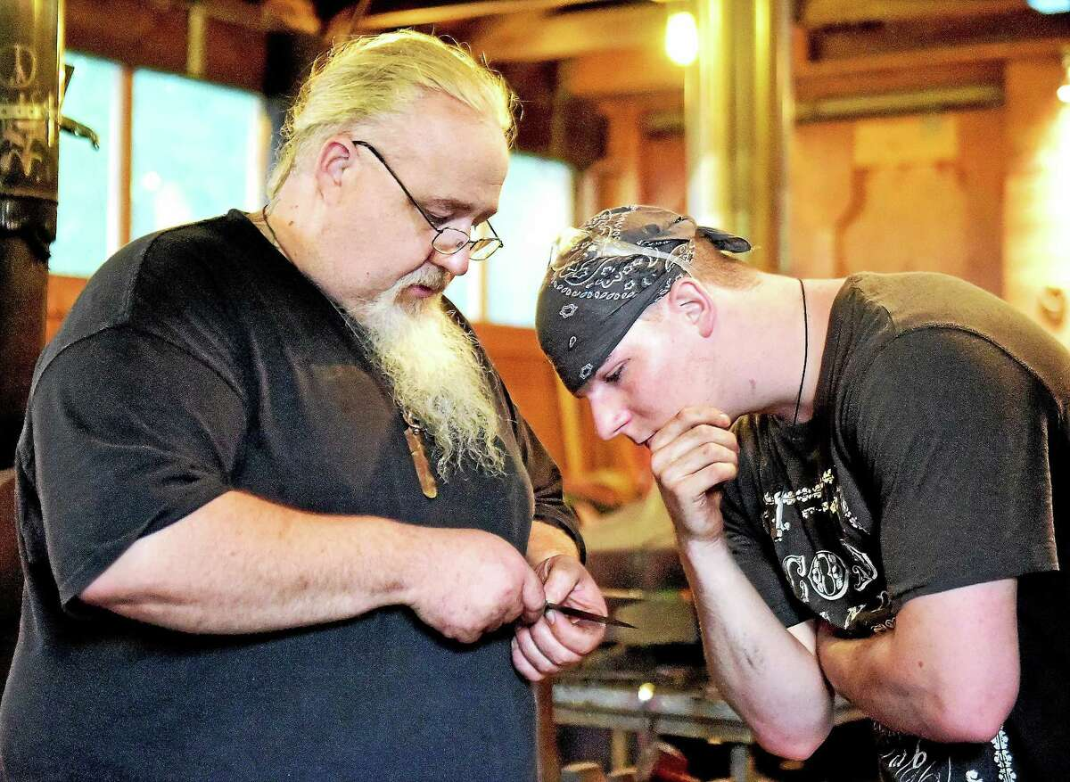 Guilford bladesmith Mace Vitale, owner of Laurel Rock Forge and rated journeyman smith with the American Bladesmith Society gives advice to Aidan Garrity, of Madison, about a small knife he is crafting in the blacksmithing class at the Guilford Art Center, Wednesday, August 13, 2015. Vitale won the History Channel's Forged in Fire.