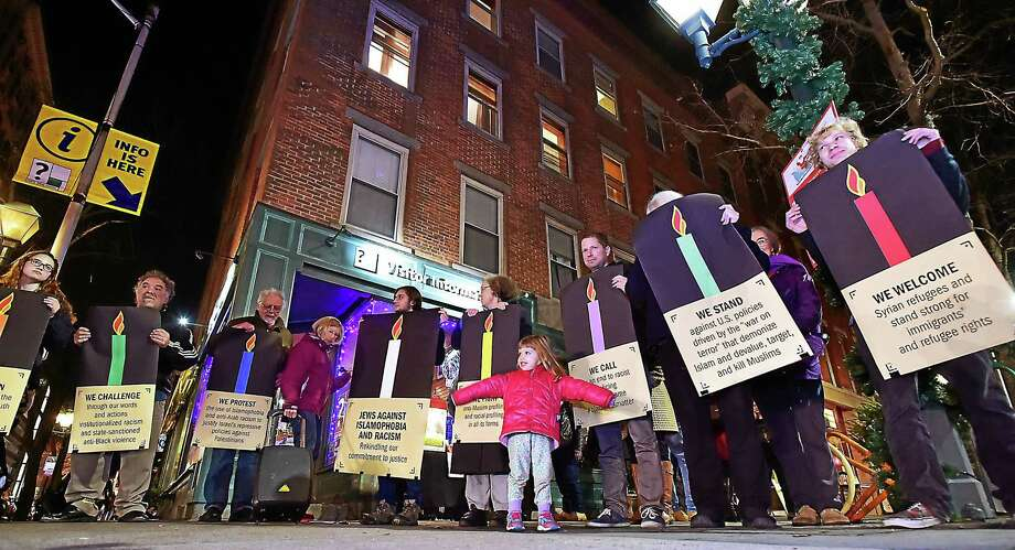 (Catherine Avalone - New Haven Register)  Activists from the New Haven Chapter of Jewish Voice For Peace hold nine signs listing commitments to fight injustice, Islamophobia and racism on the fifth day of Chanukah, Thursday, December 10, 2015, at the corner of Chapel and College Streets in New Haven. For eight nights, Jews in cities including New York City, Miami, Chicago, Washington, DC, Portland Oregon, Durham, Columbus, Seattle,Atlanta, Boston, Springfield, Itaca and Denver will hold the signs and read aloud the commitments in a public space. On the eighth and last night of Chanukah, all the cities will rekindle their commitments. Photo: Journal Register Co. / New Haven RegisterThe Middletown Press