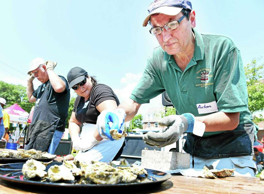 Annie Bonifacio (center) of North Carolino peers over at Anton Christen (right) of the Union Oyster House in Boston, Massachusetts, as Bob Hastings (left) of Pennsylvania finishes during an oyster shucking contest at the 41st Annual Milford Oyster Festival on 8/15/2015. Photo: (Arnold Gold-New Haven Register)