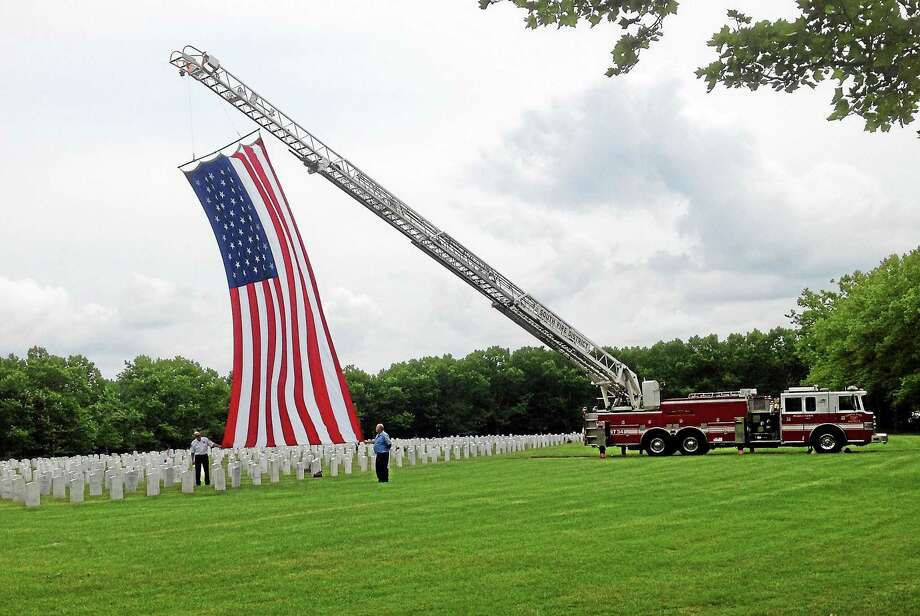 "A large American flag flew from the ladder of Middletown Fire Department's Truck No. 34 during Wednesday's ceremony at the Connecticut Veterans Cemetery where four ""forgotten"" soldiers were laid to rest. Photo: Jeff Mill — The Middletown Press"