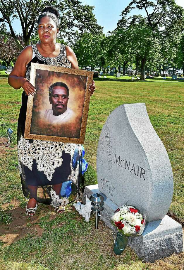 Delores McNair stands near the grave of her husband, Darryl W. McNair, holding a portrait of her deceased husband, Saturday, August 15, 2015. Darryl W. McNair was killed by a stray bullet on his 58th birthday, August, 17, 2014, in New Haven and the case remains unsolved. McNair left behind his mother, Shirley McNair, of New Jersey and five children, Douglas Costin, of Pennsylvania, Chandra Costin, of New Haven, Martis Costin, of New Haven, Tammy Mathews of New Jersey and Takesha Mathews, of Virginia. Photo: (Catherine Avalone - New Haven Register)      / New Haven RegisterThe Middletown Press