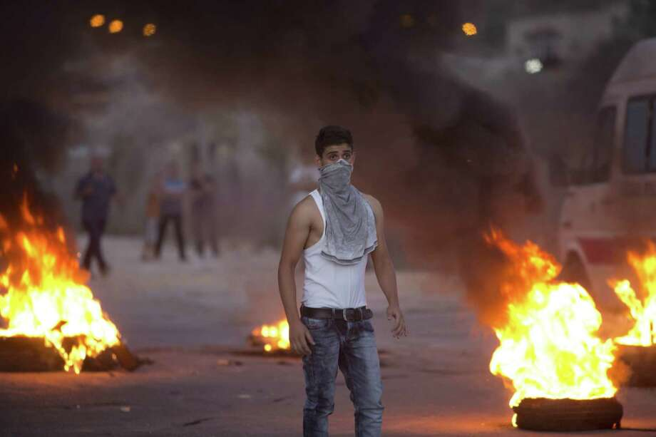 A Palestinian demonstrator burns tires during clashes with Israeli soldiers after Palestinian Rafeq Ahmad al-Taj, 21, was shot and killed by an Israeli policeman after he stabbed a policeman, in the village of Beita south of the West Bank city of Nablus, Aug. 15, 2015. Israeli police spokeswoman Luba Samri said al-Taj approached officers conducting a security check and stabbed one in the back with a knife, moderately wounding him. An officer nearby opened fire and killed al-Taj. Photo: (AP Photo/Majdi Mohammed) / AP
