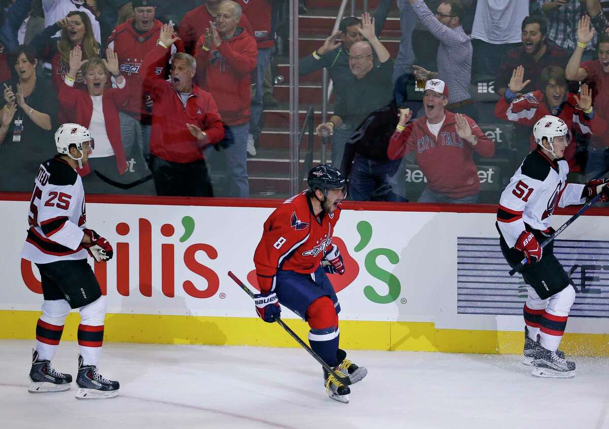 Capitals left wing Alex Ovechkin (8) celebrates his goal between New Jersey Devils centers Stefan Matteau (25) and Sergey Kalinin (51) during Saturday's game in Washington.