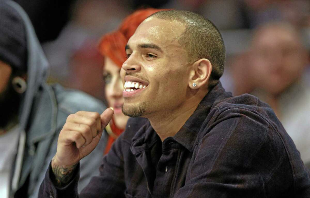 In this Feb. 26, 2012 photo, Grammy-winning singer Chris Brown sits on the sidelines during the second half of the NBA All-Star basketball game in Orlando, Fla.
