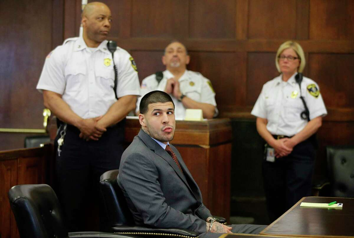 Former New England Patriots NFL football player Aaron Hernandez sits at the defendant's table while his attorneys participate in a sidebar discussion during his arraignment at Suffolk Superior Court on May 21, 2015 in Boston, on a charge of trying to silence a witness in a double murder case against him by shooting the man in the face.