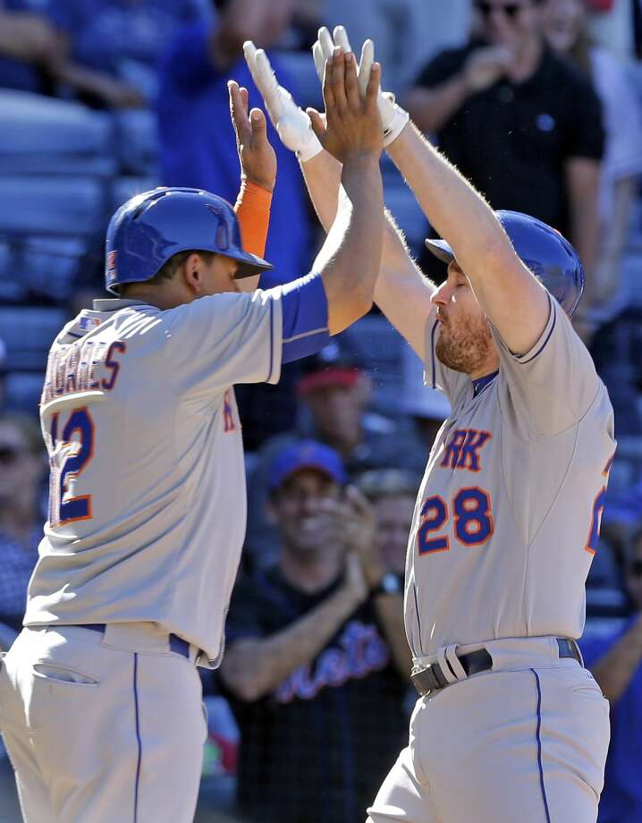 The Mets' Daniel Murphy (28) celebrates with teammate Juan Lagares (12) after he hit a three-run home run in the ninth inning Sunday. Photo: Butch Dill — The Associated Press   / FR111446 AP