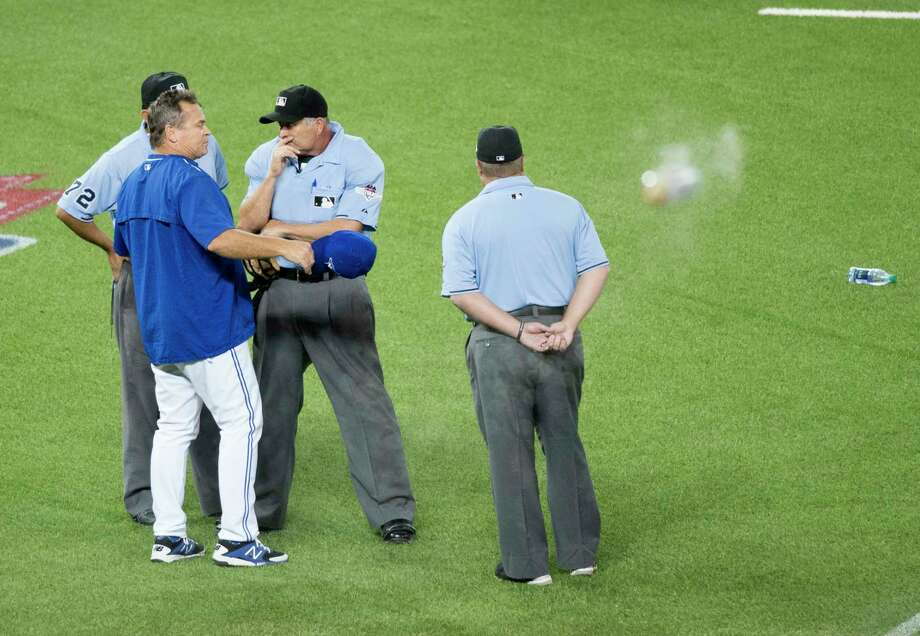 Toronto Blue Jays manager John Gibbons, left, argues with members of the umpire crew as bottles are thrown on the field during the seventh inning in Game 5 of the American League Division Series against the Texas Rangers. The crowd was incensed when umpires allowed the tie-breaking run to score after Toronto catcher Russell Martin's throw back to the pitcher deflected off hitter Shin-Soo Choo's bat and allowed the tiebreaking to score. The Blue Jays rallied to win 6-3. Photo: Darren Calabrese/The Canadian Press Via AP   / CP