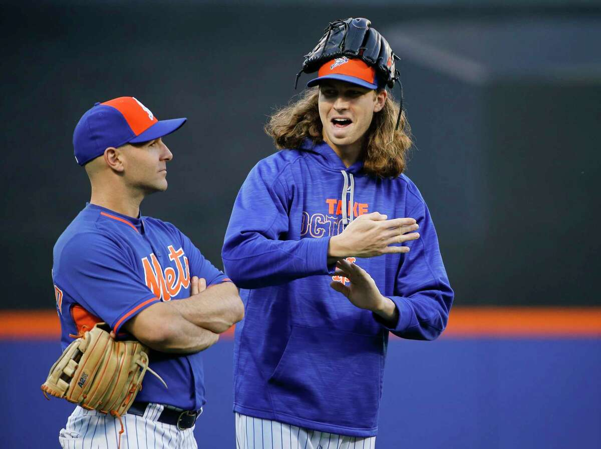 Mets bullpen catcher Dave Racaniello, left, and pitcher Jacob deGrom talk in the outfield on Tuesday night The Mets will start deGrom tonight in Game 5 of the National League Division Series against the Dodgers, with the winner moving on to face the Cubs in the National League Championship Series.