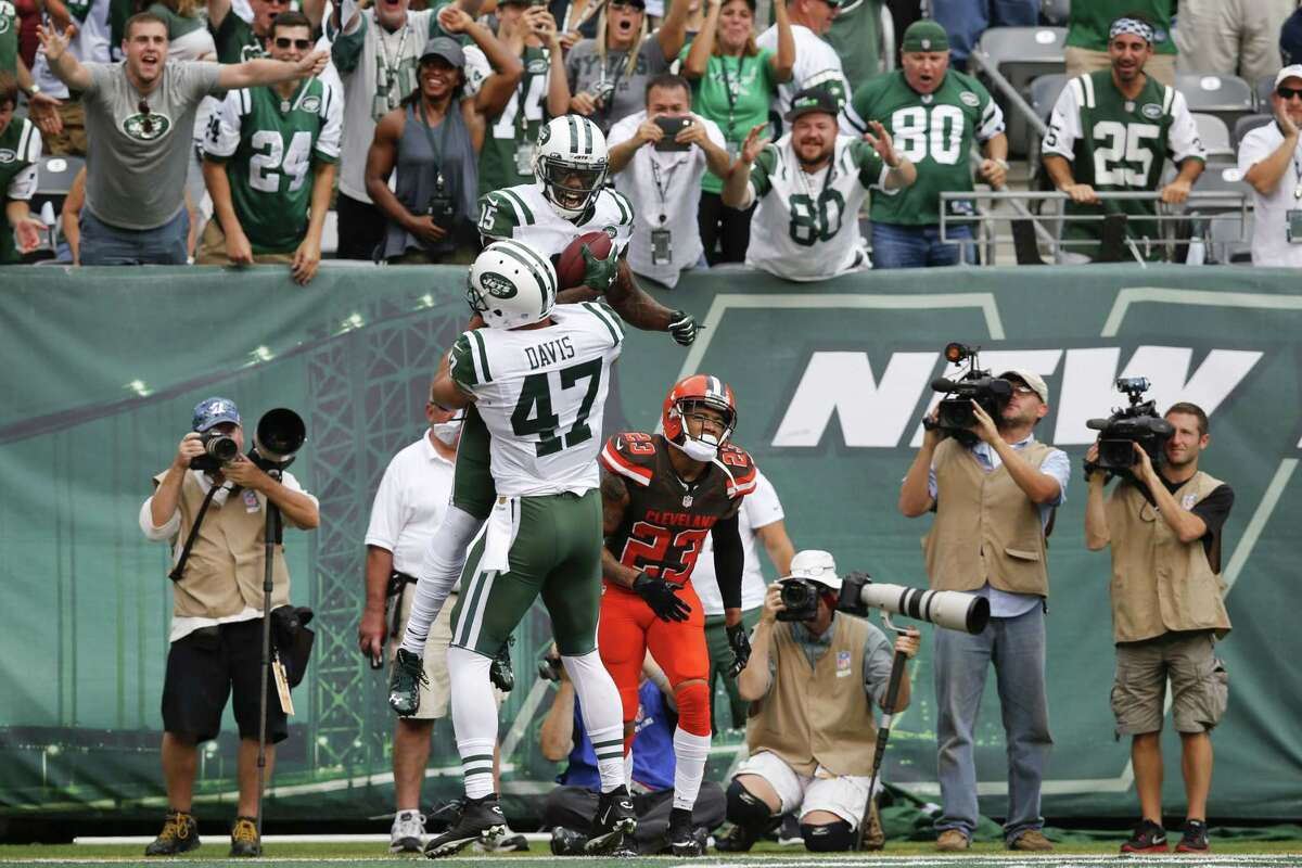 Jets wide receiver Brandon Marshall (15) celebrates with teammate Kellen Davis after catching a pass for a touchdown during the second half Sunday.
