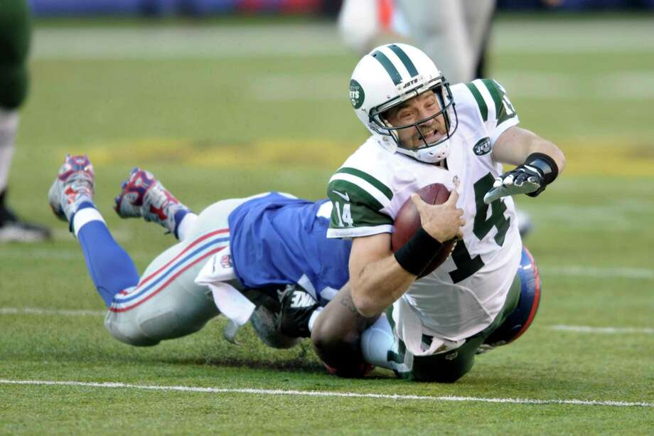 Jets quarterback Ryan Fitzpatrick is tackled by Giants defensive end Damontre Moore on Sunday. Photo: Bill Kostroun — The Associated Press   / FR51951 AP