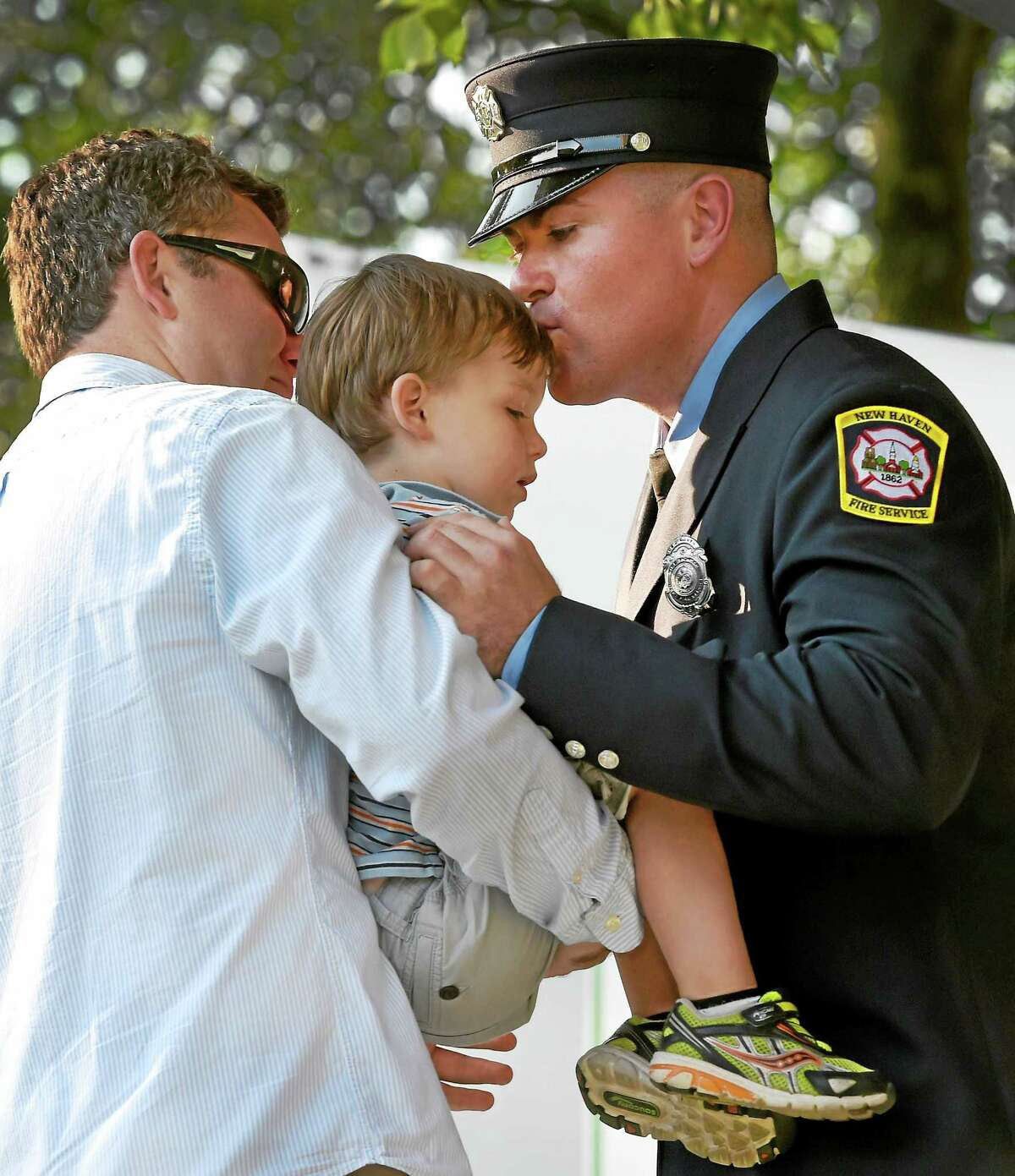 New Haven probationary firefighter Patrick Sheiffele kisses his nephew Charles Scheiffele, 3, of North Branford after he and his brother Stephen Scheiffele pinned on his badge during a graduation ceremony for the New Haven Fire Department's 58th recruit class on the New Haven Green Monday evening, July 13, 2015 for 18 new probationary firefighters.