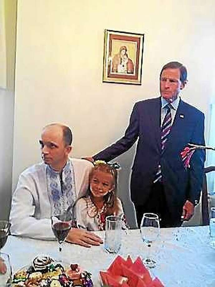 Anastasia Lutsiuk, 7, sits on the lap of her dad, Roman Lutsiuk, as U.S. Sen. Richard Blumenthal looks on. Photo: Mary O'Leary — New Haven Register
