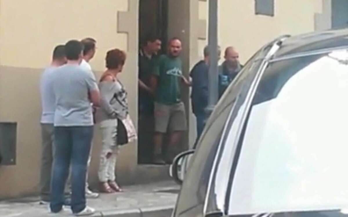 In this image from TV taken on Sept. 11, 2015, authorities lead suspect Miguel Angel Munoz, center in green, out of a building, in Grandas de Salime, northwest Spain. A body found on a rural property in northwest Spain is most likely that of an American woman who went missing while walking along a pilgrimage route, officials said Saturday.
