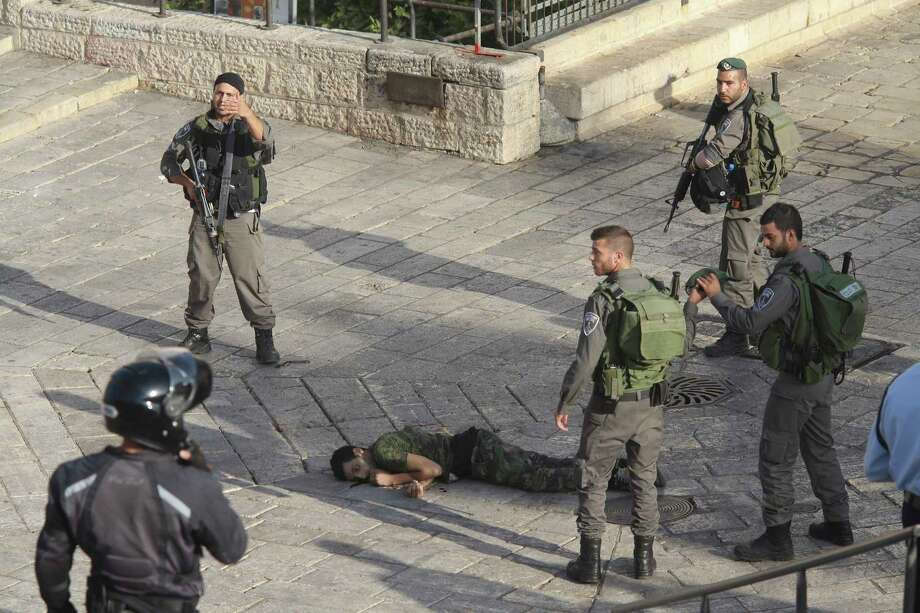 Israeli police stand around a Palestinian shot after he allegedly tried to stab a person at Damascus Gate of the Jerusalem's Old City, Wednesday, Oct. 14, 2015, Israeli police said. Photo: AP Photo/Oren Ziv    / AP