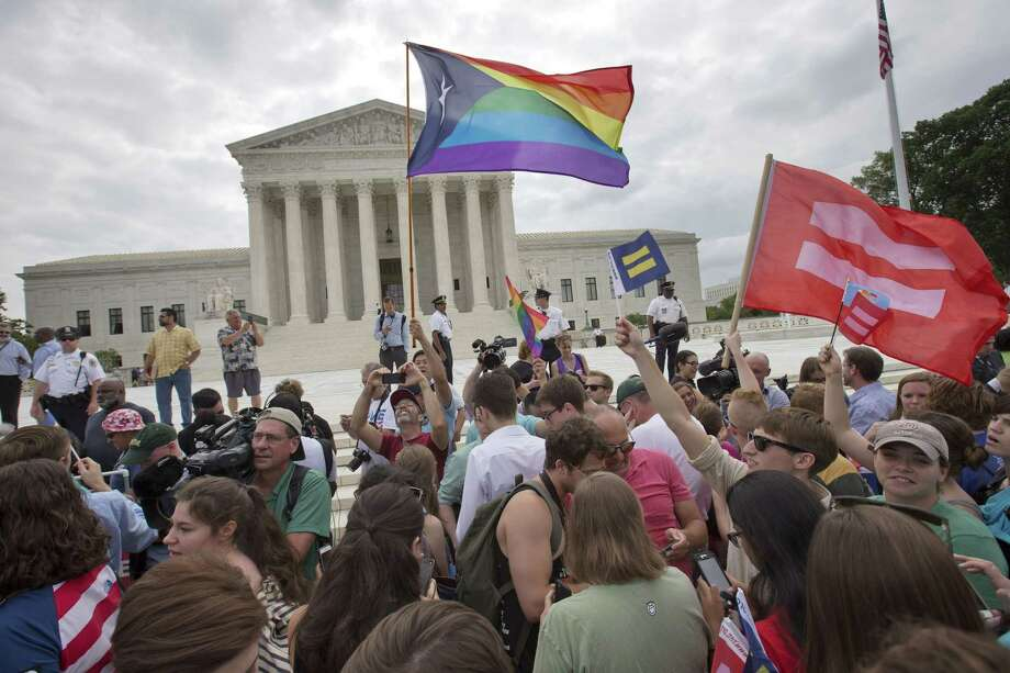 The crowd reacts as the ruling on same-sex marriage was announced outside of the Supreme Court in Washington, Friday June 26, 2015. The Supreme Court declared Friday that same-sex couples have a right to marry anywhere in the US. Photo: AP Photo/Jacquelyn Martin   / AP