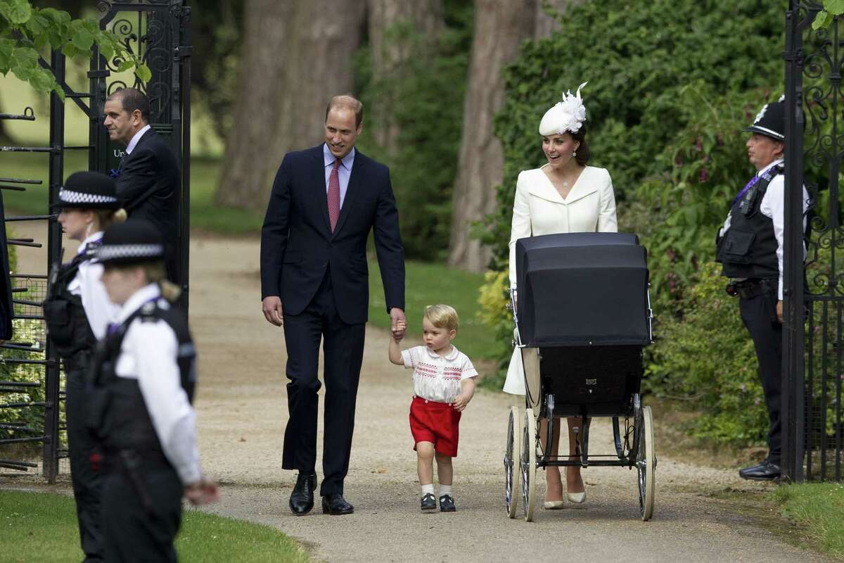FILE- In this file photo dated Sunday, July 5, 2015, Britain's Prince William, Kate the Duchess of Cambridge, their son Prince George walk with their daughter Princess Charlotte in a pram, during an official media event as they arrive for Charlotte's Christening at St. Mary Magdalene Church in Sandringham, England. Royal officials at Kensington Palace are urging all media organizations not to publish images of Prince George and Princess Charlotte, by some paparazzi photographers who are using increasingly dangerous tactics to snap images of the royals, which presents a risk ìin a heightened security environment.íí (AP Photo/Matt Dunham, FILE)