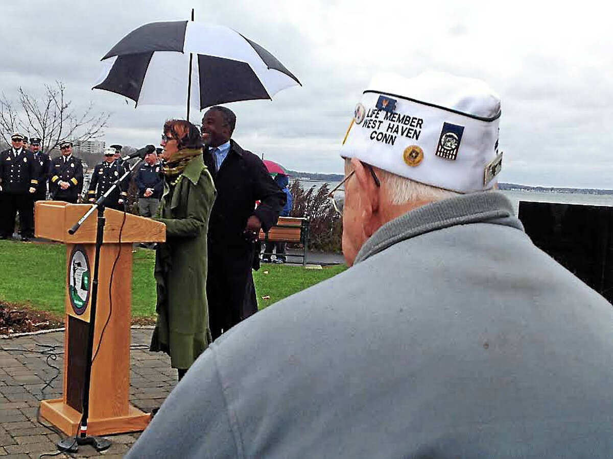 U.S. Rep. Rosa L. DeLauro, D-3, speaks at West Haven's Veterans Day ceremony Wednesday. Master of Ceremonies John Lewis, West Haven Mayor Ed O'Brien's executive assistant, holds the umbrella. In the foreground is AMVETS Post 1 Chaplain Francis Blanchette, a World War II-era Army veteran.