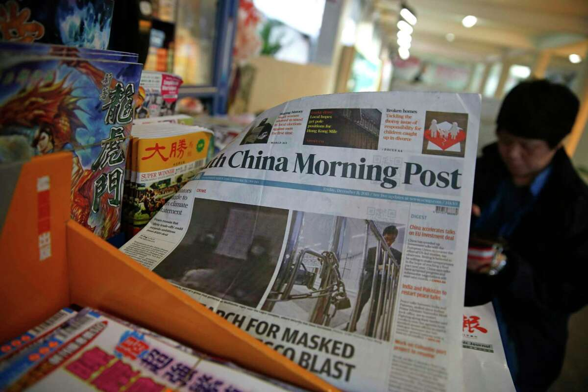 The front page of South China Morning Post is flipped by the wind as a vendor sits at her news stand in Hong Kong, Friday, Dec. 11, 2015. Chinese e-commerce giant Alibaba says it's buying Hong Kong's leading English language newspaper, the South China Morning Post. Alibaba Group said late Friday it signed a deal with publisher SCMP Group to buy the Post and the company's other media assets, which also include magazines, outdoor advertising and digital media.