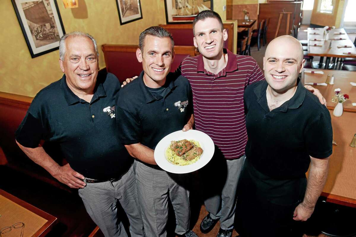 Salvatore Scotto, left, with his three sons, Antonio, holding Italian Sausage Rolled in Veal, Lorenzo and Sean, at Aniello Pizza and Italian Restaurant in East Haven.