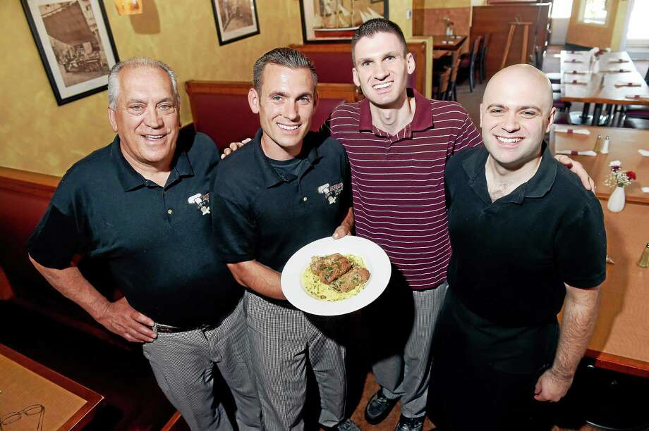Salvatore Scotto, left, with his three sons, Antonio, holding Italian Sausage Rolled in Veal, Lorenzo and Sean, at Aniello Pizza and Italian Restaurant in East Haven. Photo: Arnold Gold — New Haven Register