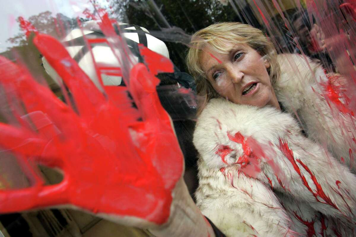 In this Oct. 2, 2006, file photo, People for the Ethical Treatment of Animals (PETA) President Ingrid Newkirk protests the use of animal fur in fashion in a Jean-Paul Gaultier shop in Paris after spraying red paint on the shop window. PETA turns 35 years old in 2015, is the largest animal rights group in world with 3 million members, and has done a lot with a little sex, shock and celebrity.