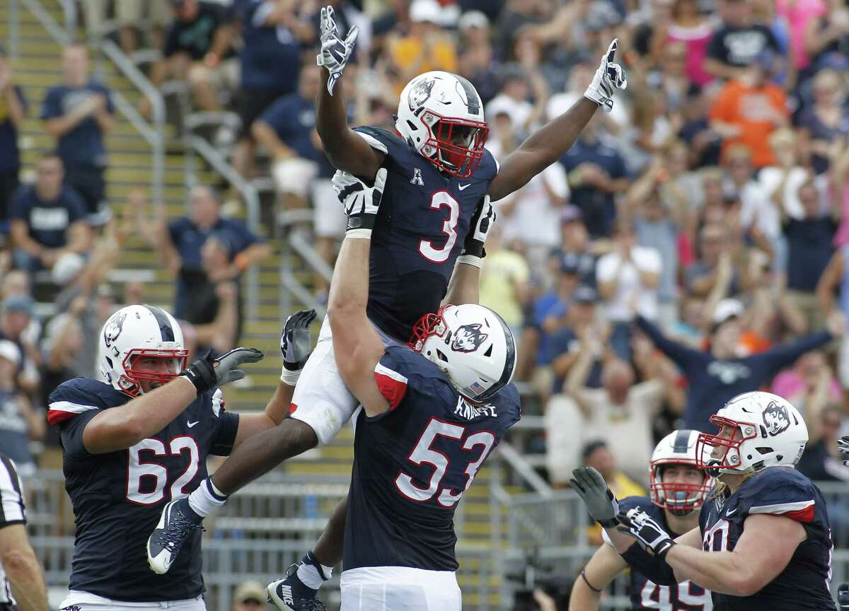 UConn running back Ron Johnson is lifted into the air by offensive lineman Andreas Knappe after scoring a touchdown during the third quarter of the Huskies' 22-17 win over Army on Saturday at Rentschler Field in East Hartford.