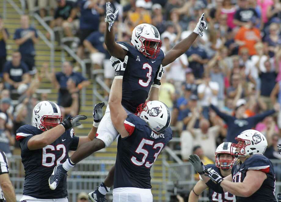 UConn running back Ron Johnson is lifted into the air by offensive lineman Andreas Knappe after scoring a touchdown during the third quarter of the Huskies' 22-17 win over Army on Saturday at Rentschler Field in East Hartford. Photo: Stew Milne — The Associated Press   / FR56276 AP