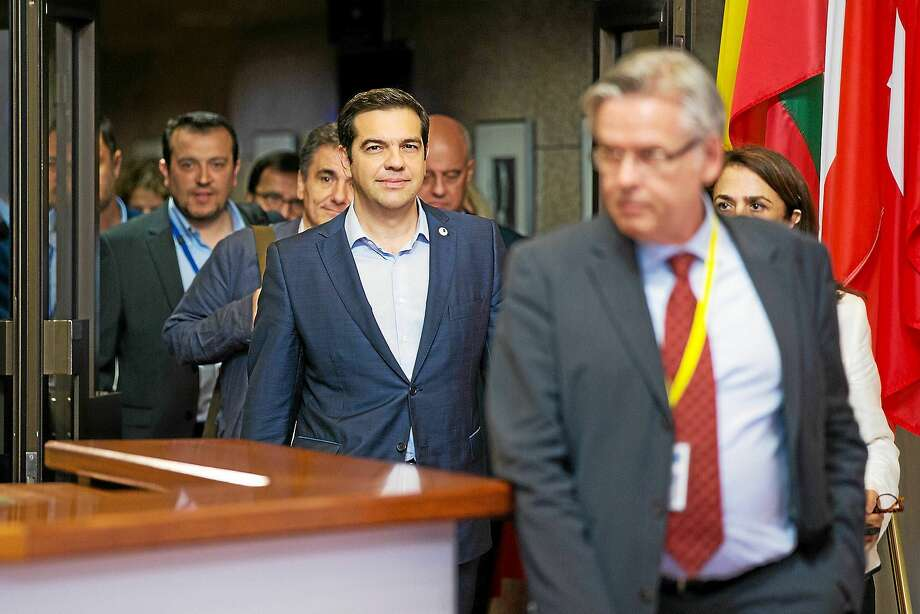 Greek prime minister Alexis Tsipras (center) reacts as Euclid Tsakalotos, Greece's finance minister (center left) walks behind as they depart following all-night bailout talks in Brussels. Making the asset-sale math work as the economy contracts will be difficult for Greek Prime Minister Tsipras, who on Monday bowed to demands from European creditors in exchange for a bailout of as much as 86 billion euros that will keep his nation in the euro zone. Photo: Bloomberg News Photo/Jasper Juinen   / BLOOMBERG NEWS