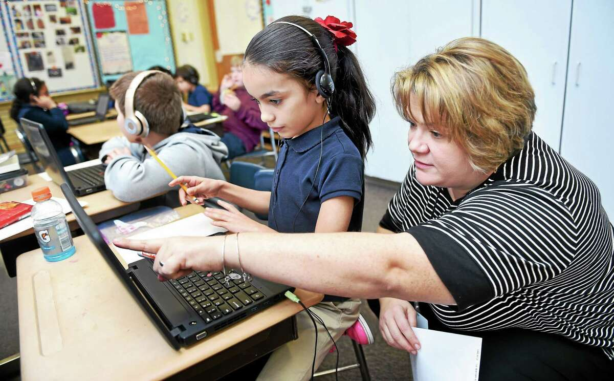 Third-grader Mikaila Matta, center, 8, gets assistance from University of New Haven intern Michele Schettino, right, during an hour of writing code at Tuttle Elementary School in East Haven Friday.